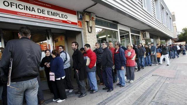 varias personas esperan a la cola de una oficina de empleo