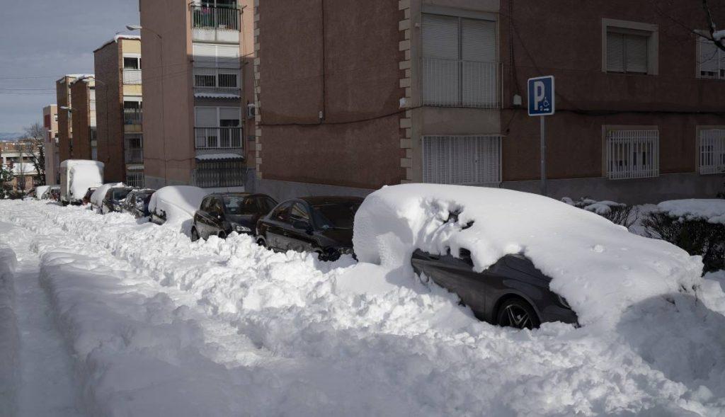 Un coche enterrado por la nieve y el hielo